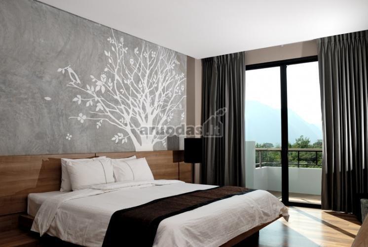 Pilka miegamojo siena, dekoruota balto medžio iškarpa