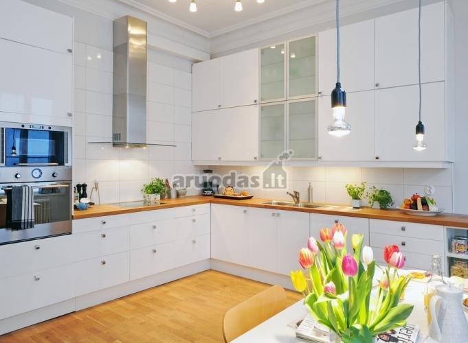 Balta virtuvė su natūralaus medžio stalviršiu