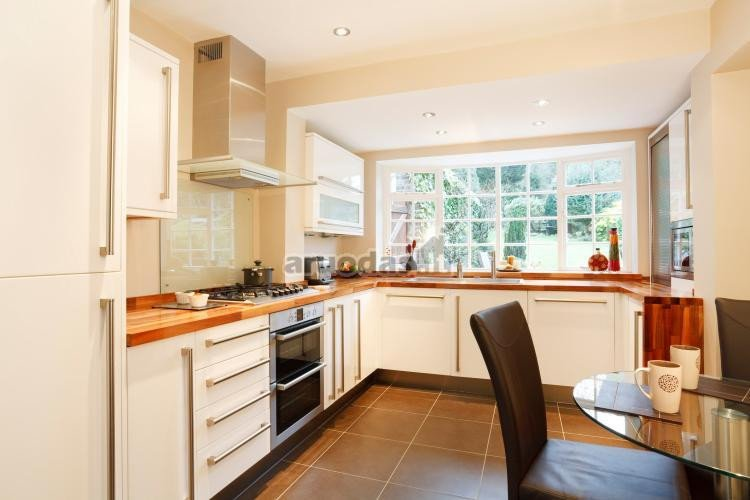Tarp kreminės ir rudos virtuvės interjeras