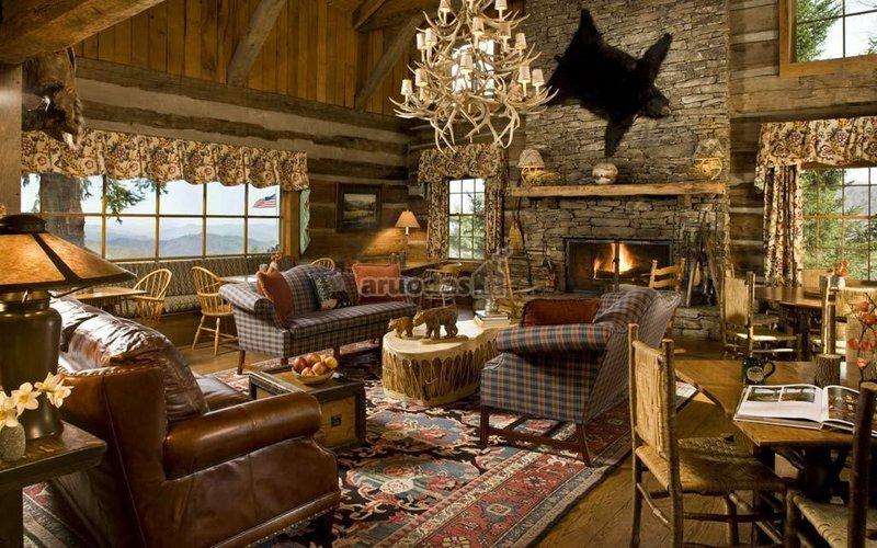 Odinė sofa ir meškos kailis virš židinio