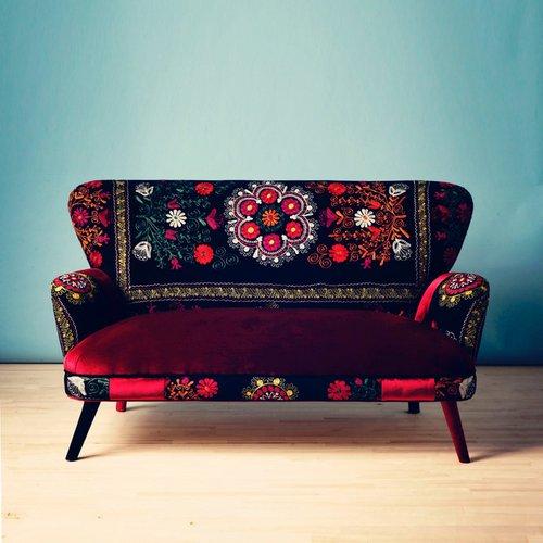 Tamsi, raštais dekoruota sofa
