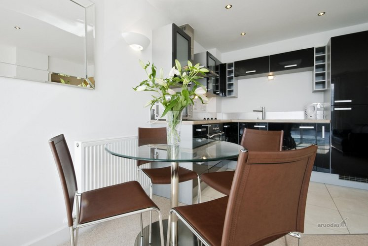 Apvalus, stiklnis valgomojo stalas ir rudos kėdės