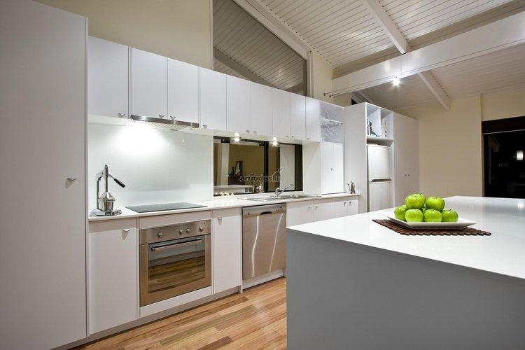 Aukštų lubų, baltas virtuvės interjeras