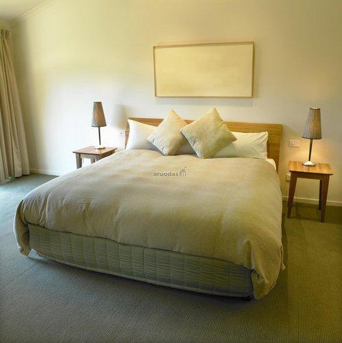 šviesus ir minkštas miegamojo interjeras