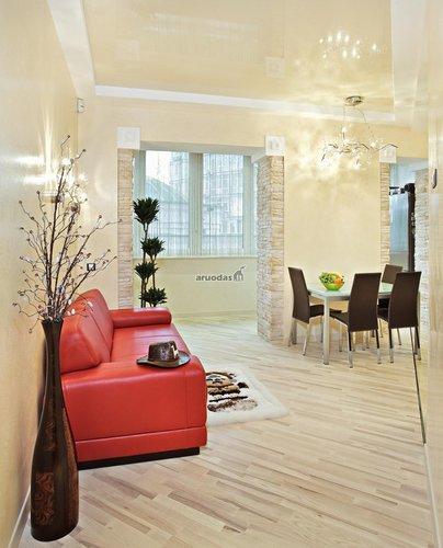 Raudona sofa - šviesaus kambario akcentas