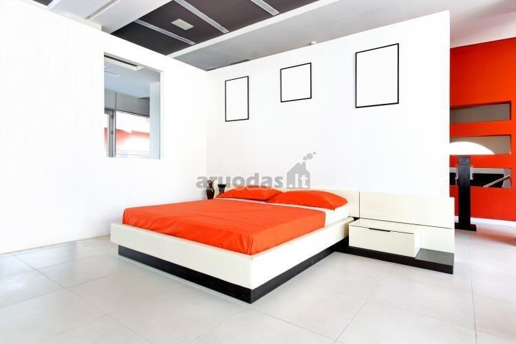 Baltas interjeras išryškintas juodais kontūrais ir oranžiniu užklotu