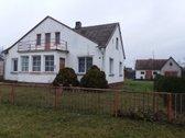 Erdvus namas su garažu ir ūkiniais pastatais.