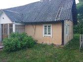 Namas stovi pačiam kaimo gale, netoli miško